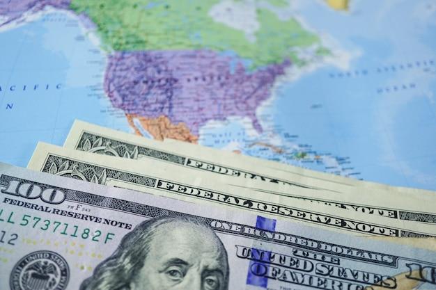 Notas de dólar dos eua no mapa do globo do mundo.