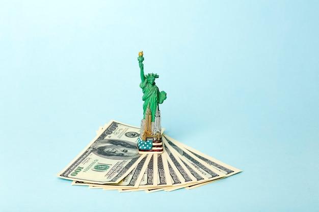 Notas de dólar dos eua sob a estátua da liberdade em um fundo azul claro