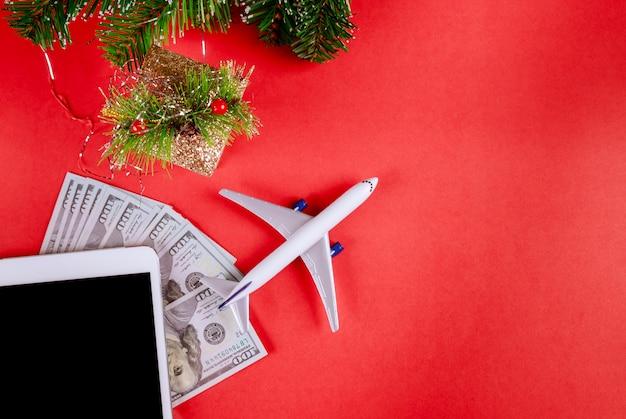 Notas de dólar dos eua, tablet de dispositivos digitais com o conceito de viagens de férias de avião modelo