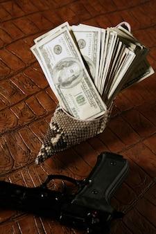 Notas de dólar e arma, pistola preta
