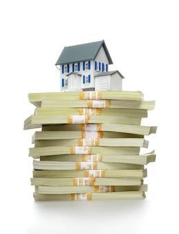 Notas de dólar e modelo de casa em fundo claro