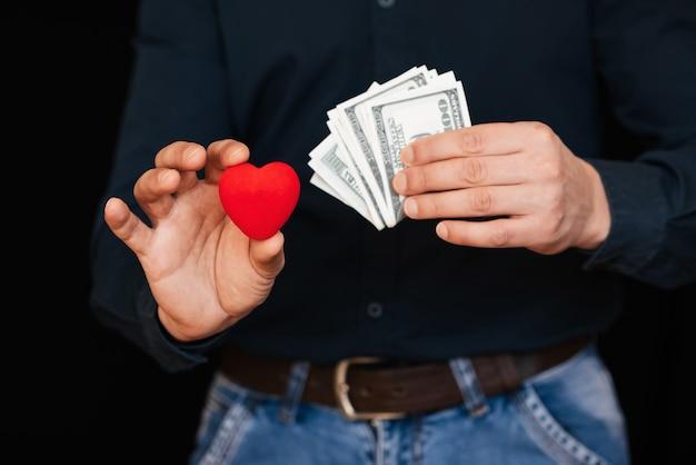 Notas de dólar e um coração vermelho nas mãos de um homem