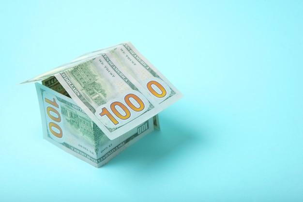 Notas de dólar e uma estatueta de uma casa em uma hipoteca de fundo colorido