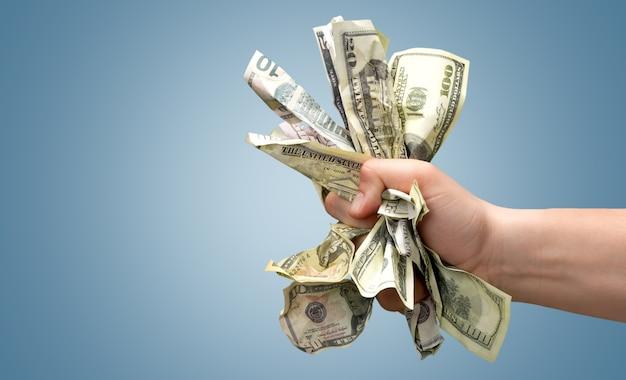 Notas de dólar em close-up em mão humana em fundo azul
