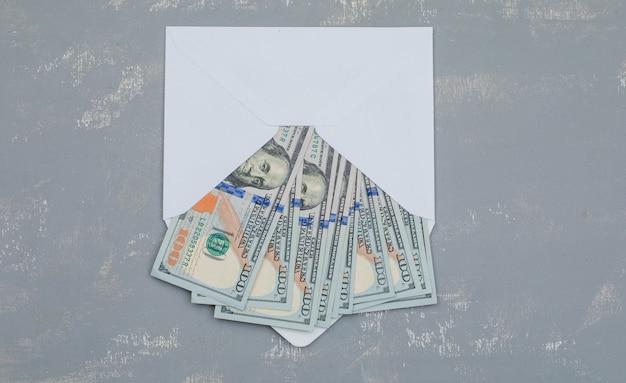 Notas de dólar em envelope aberto na mesa de gesso