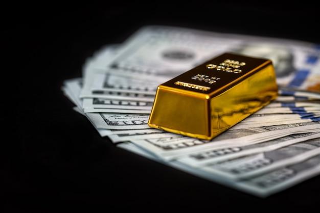 Notas de dólar em fundo preto com barras de ouro