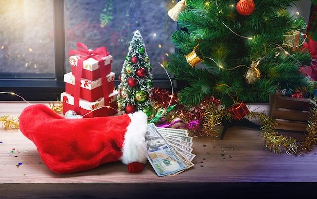 Notas de dólar em santa meia e fundo de decoração de natal