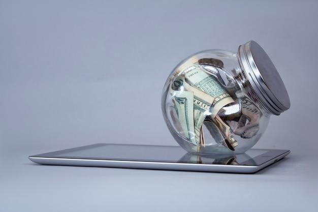 Notas de dólar em um cofrinho de vidro em um tablet.