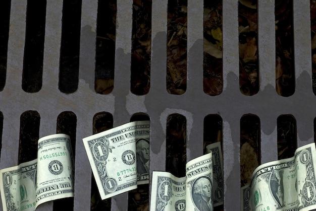 Notas de dólar em um dreno rua