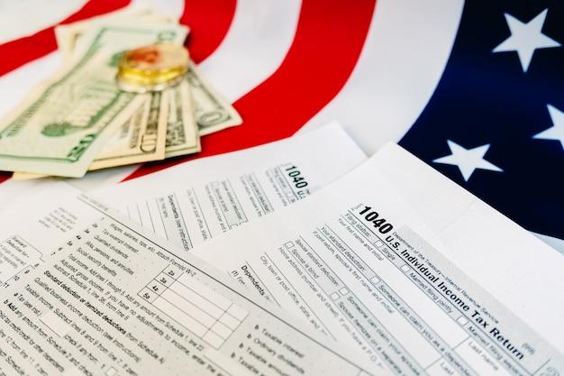 Notas de dólar em uma tabela na qual o formulário de pagamento de imposto americano 1040 é preenchido.