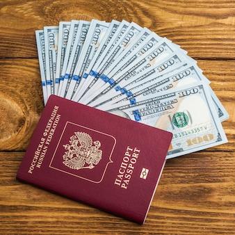 Notas de dólar em ventilador e passaporte em fundo de madeira.