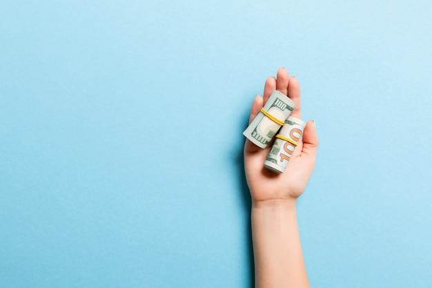 Notas de dólar enroladas em tubos na palma da mão feminina