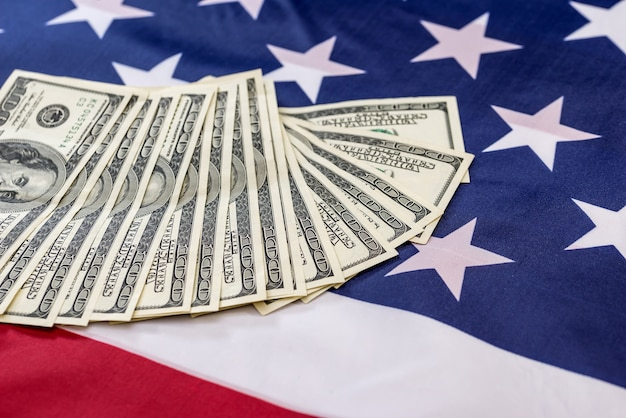 Notas de dólar na bandeira americana fecham