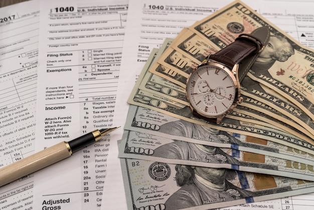 Notas de dólar no formulário de imposto de 1040 com caneta