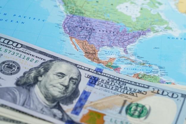 Notas de dólar no mapa do globo do mundo eua