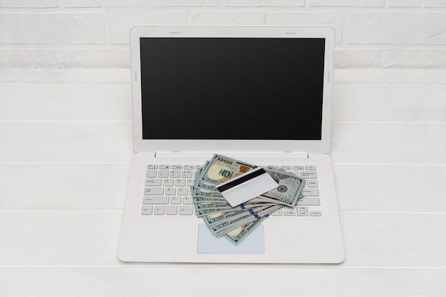 Notas de dólar no teclado do laptop e no cartão de crédito