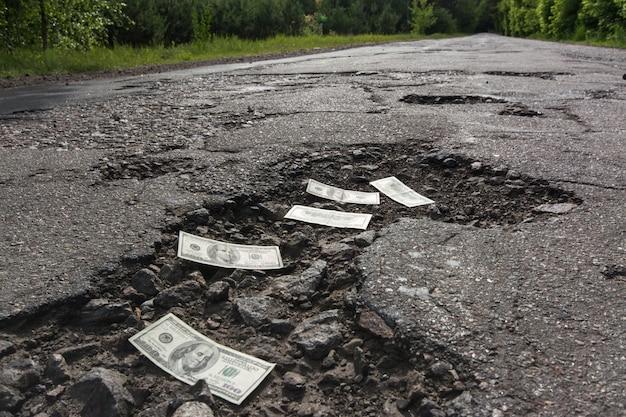 Notas de dólar nos buracos na estrada