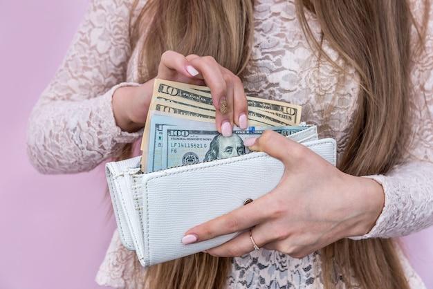 Notas de dólar tiradas da bolsa por mãos femininas