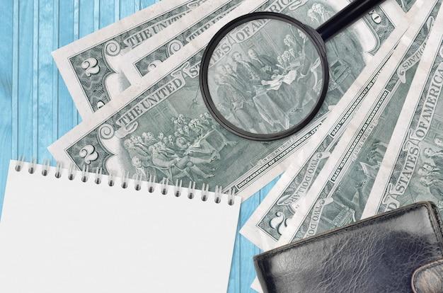 Notas de dólares americanos e lupa com bolsa preta e bloco de notas