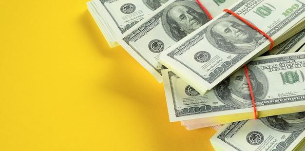 Notas de dólares americanos em pacotes sobre um fundo amarelo brilhante.