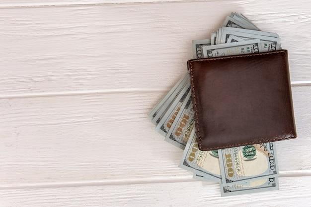 Notas de dólares em uma carteira de couro escuro, fundo financeiro