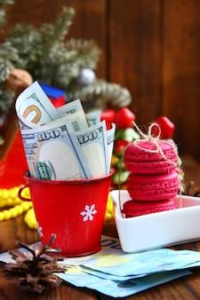 Notas de dólares torcidas no balde de natal vermelho, biscoitos de euro e rosa