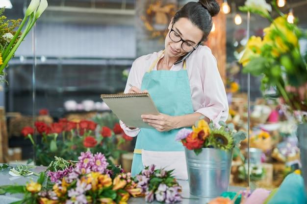 Notas de escrita de florista falando pelo smartphone