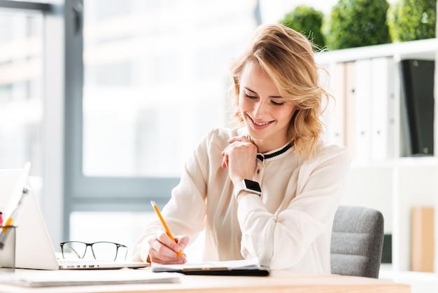 Notas de escrita de mulher de negócios jovem feliz.
