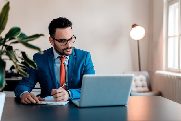 Notas de escrita de trabalho do homem de negócios novo que sentam-se em um desktop no escritório.