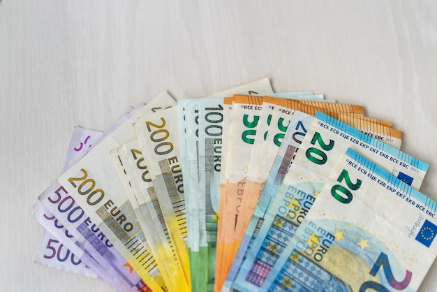 Notas de euro coloridas em leque na mesa de madeira Foto Premium