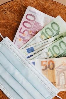 Notas de euro com máscaras em uma mesa de madeira