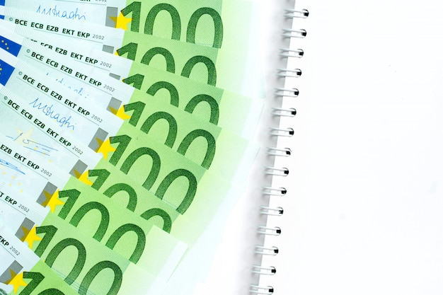 Notas de euro e bloco de notas vazio no fundo branco