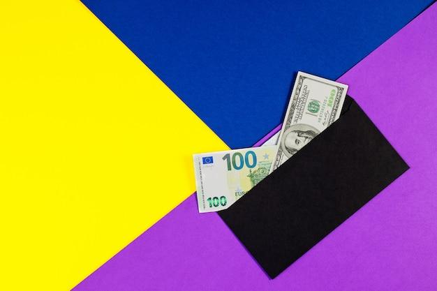 Notas de euro e dólar americano em envelope preto sobre fundo de papel de cor.