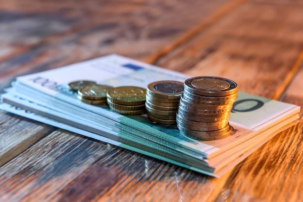 Notas de euro e moedas de cêntimos de euro em fundo de madeira