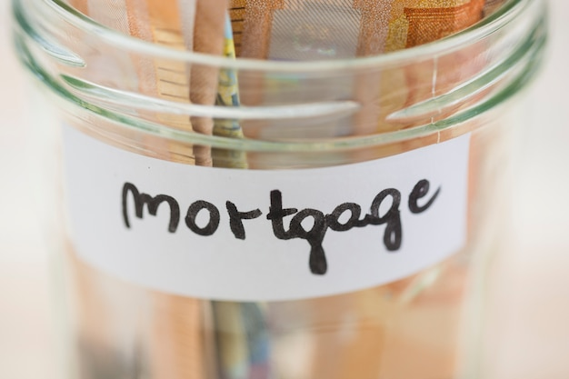 Notas de euro economizando para a hipoteca no frasco de vidro