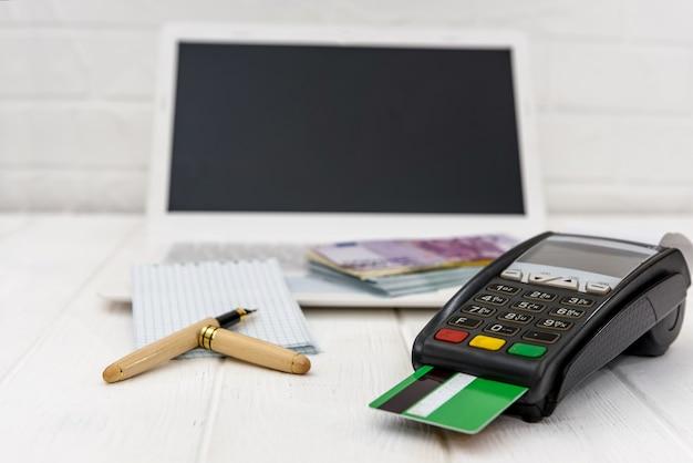 Notas de euro em laptop e terminal bancário