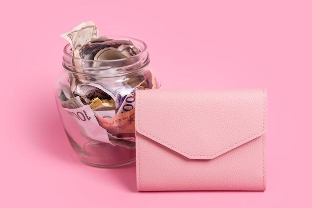 Notas de euro em um frasco de vidro com uma carteira rosa sobre fundo rosa