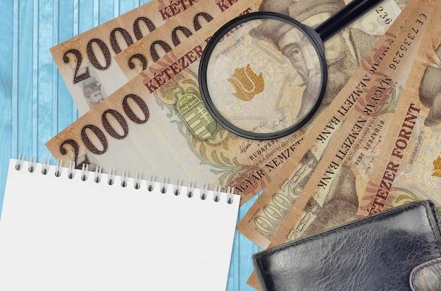 Notas de forinto húngaro de 2000 e lupa com bolsa preta e bloco de notas
