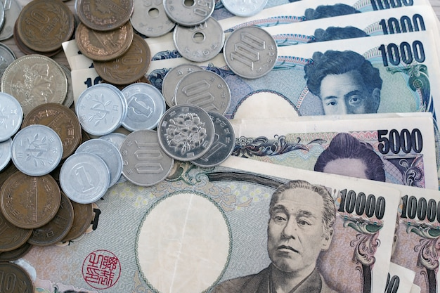 Notas de ienes japoneses e moedas de iene japonês para fundo de conceito de dinheiro