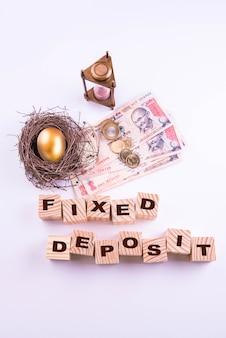 Notas de moeda indiana com moedas e ovo de ouro junto com relógio de areia antigo e blocos de madeira com fundos mútuos ou depósito fixo escrito sobre eles