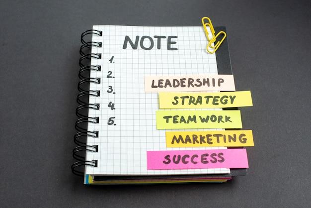 Notas de negócios de motivação de vista frontal com bloco de notas em fundo escuro