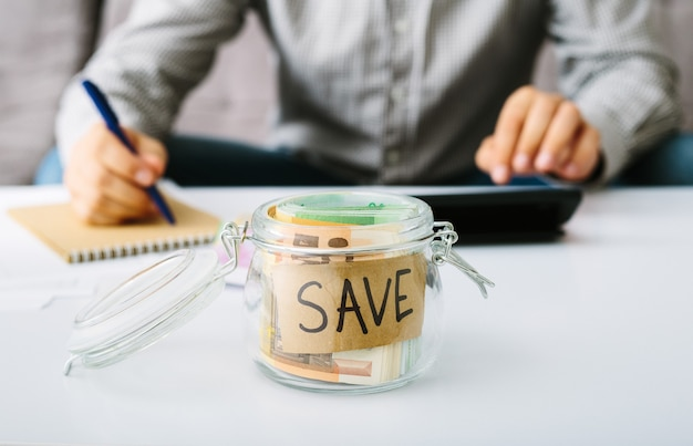 Notas de notas de euro em uma garrafa de vidro para economizar. homem fazendo sua contabilidade. pequenos negócios: depósitos e empréstimos, redução das taxas de juros.