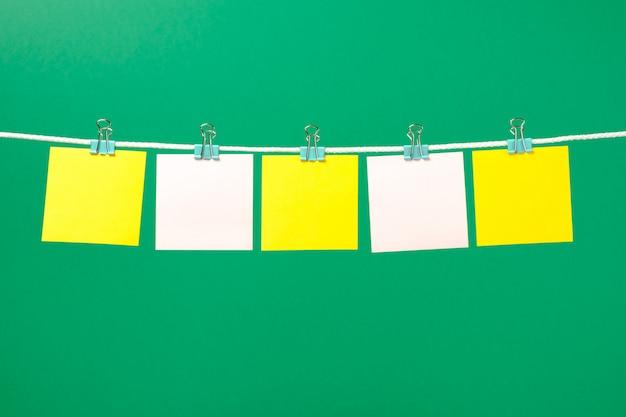 Notas de papel em branco amarelo e rosa na corda