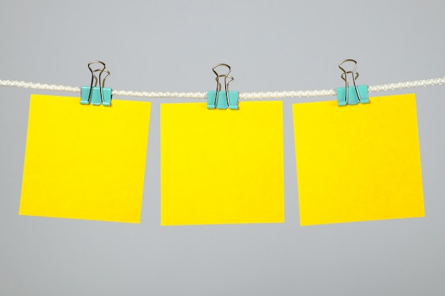 Notas de papel em branco amarelo pendurado no varal