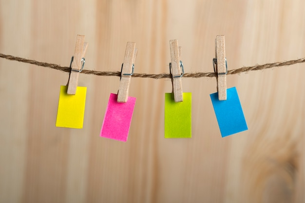 Notas de papel multicoloridas penduradas com prendedores de roupa na corda. copie o espaço. lugar para o seu texto. nota, lembrete.