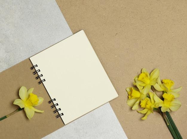 Notas de papel ofício, flores amarelas em pedra e mesa de madeira