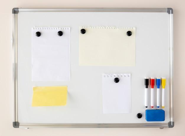 Notas de papel presas ao quadro magnético branco com ímãs.
