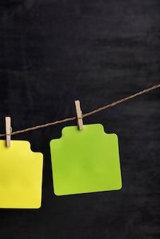 Notas de papel verde em branco penduradas com prendedor de roupa na corda. copie o espaço. lugar para o seu texto. fundo preto.