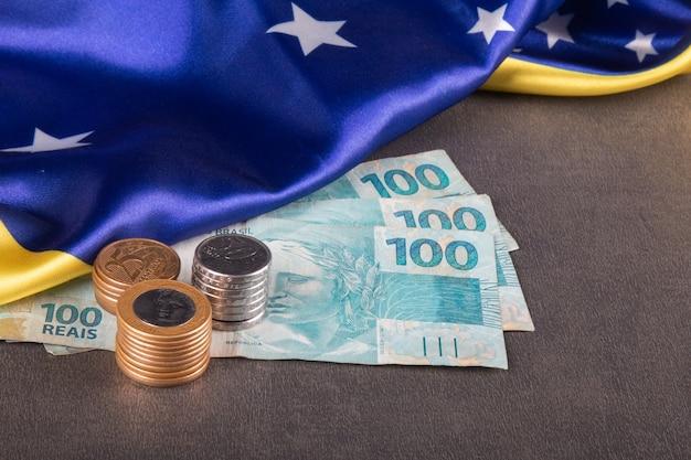 Notas e moedas de cem reais sobre bandeira brasileira.