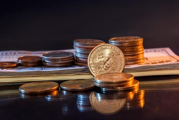Notas e moedas de dólar em fundo escuro